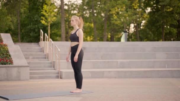 Fitness-Frau praktiziert Yoga-Übungen auf Matte im Freien City Street Sonnenlicht Hintergrund
