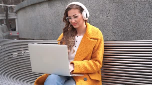 Obchodní žena nosit brýle poslouchat hudbu sluchátka venkovní sedací souprava pomocí notebooku venkovní