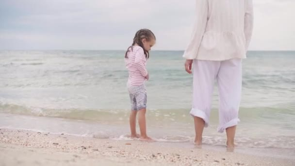 Mother With Little Daughter Walking Along the Sea Happy Family on the Beach Mother holds hand little child walking along the seashore. Traveling Summer Vacation
