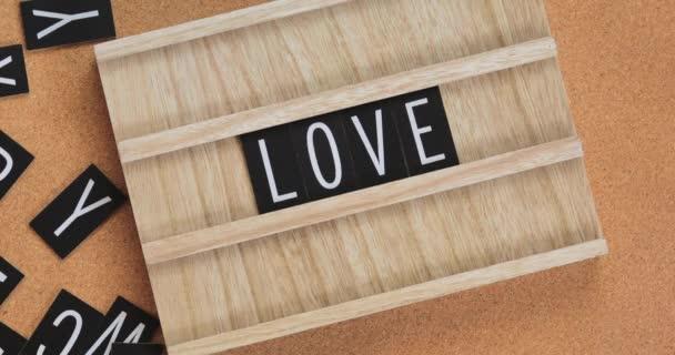 Dámské ruce složit slovo LOVE z písmen a dát kytici růžových tulipánů vedle něj. Horní pohled. Plocha.