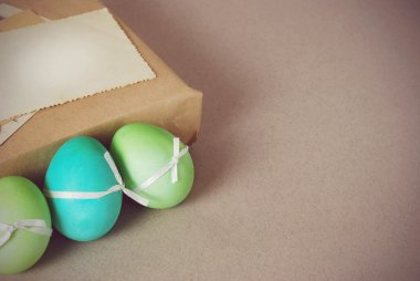 Vintage still life with easter eggs, white bunny and gift boxes in craft paper
