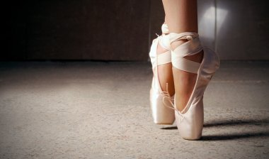 Feet of ballerina dancing in ballet shoes