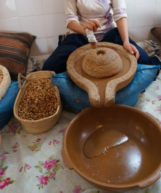 A moroccan worker preparing argan oil