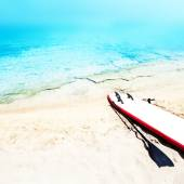 Holiday beach sunny seascape with surf board, sand and ocean. Su