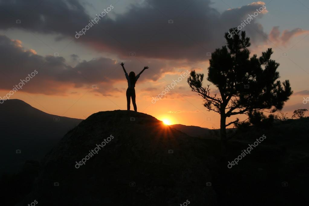 Silhouette of a girl standing on a mountain with his hands up ag