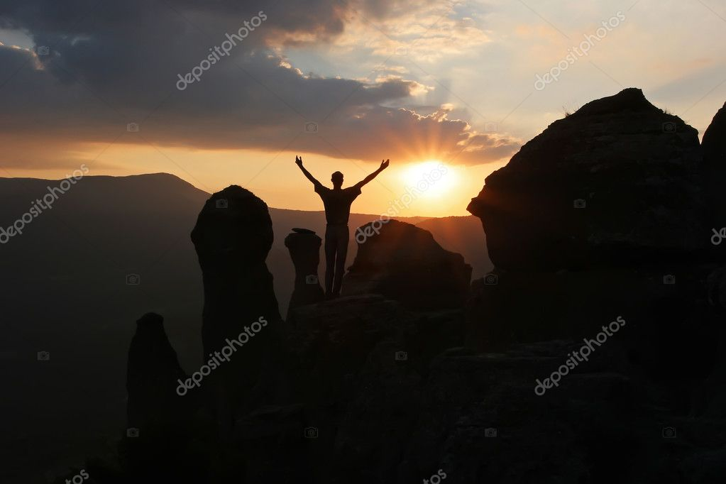 A man stands on the mountain raising his hands up and greets the