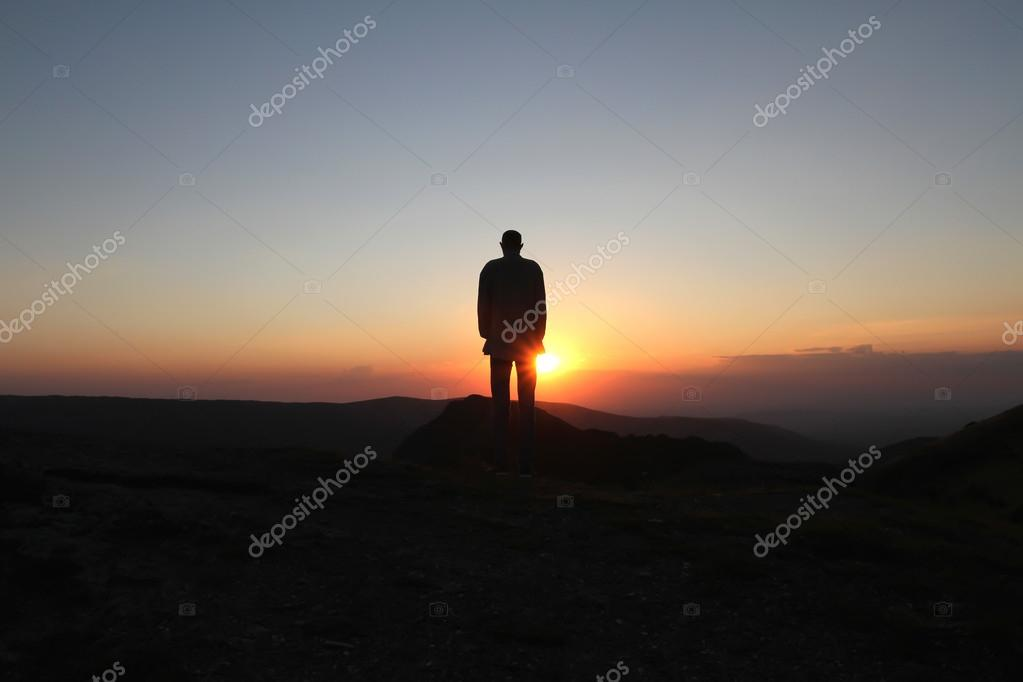 A man stands on the mountain and greets the rising sun
