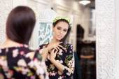 Beautiful Girl Looking in the Mirror and Trying on Floral Dress