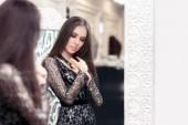 Fotografie Girl in Black Lace Dress Looking in the Mirror