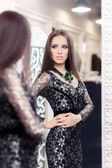 Fotografie Girl in Black Lace Dress Looking in the Mirror