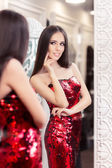 Fotografie Beautiful Girl in Red Sequin Dress Looking in the Mirror