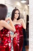 Fotografie Beautiful Girl in Red Sequin Dress Looking in the Mirror
