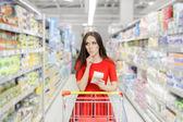 Fényképek Kíváncsi nő a szupermarket, a bevásárló lista