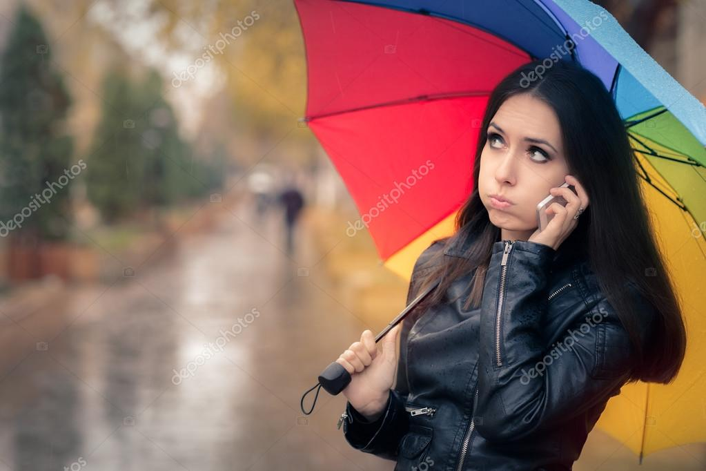 Autumn Girl Holding a Rainbow Umbrella and a Smartphone