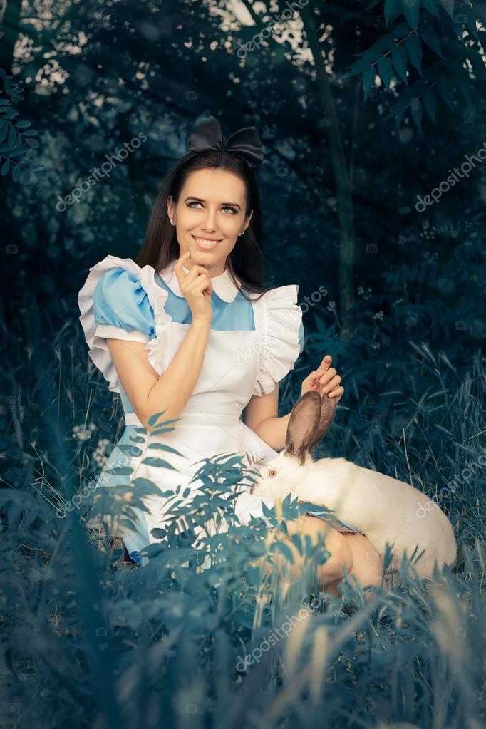 386bba37b Chica disfrazada como Alicia en el país de las maravillas con el conejo  blanco– imagen de stock