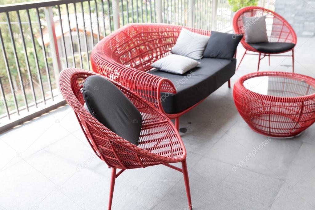 Rode rieten stoel en bank met bruine kussen op het balkon