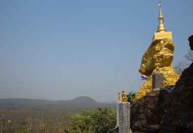golden buddhism pagoda on big stone