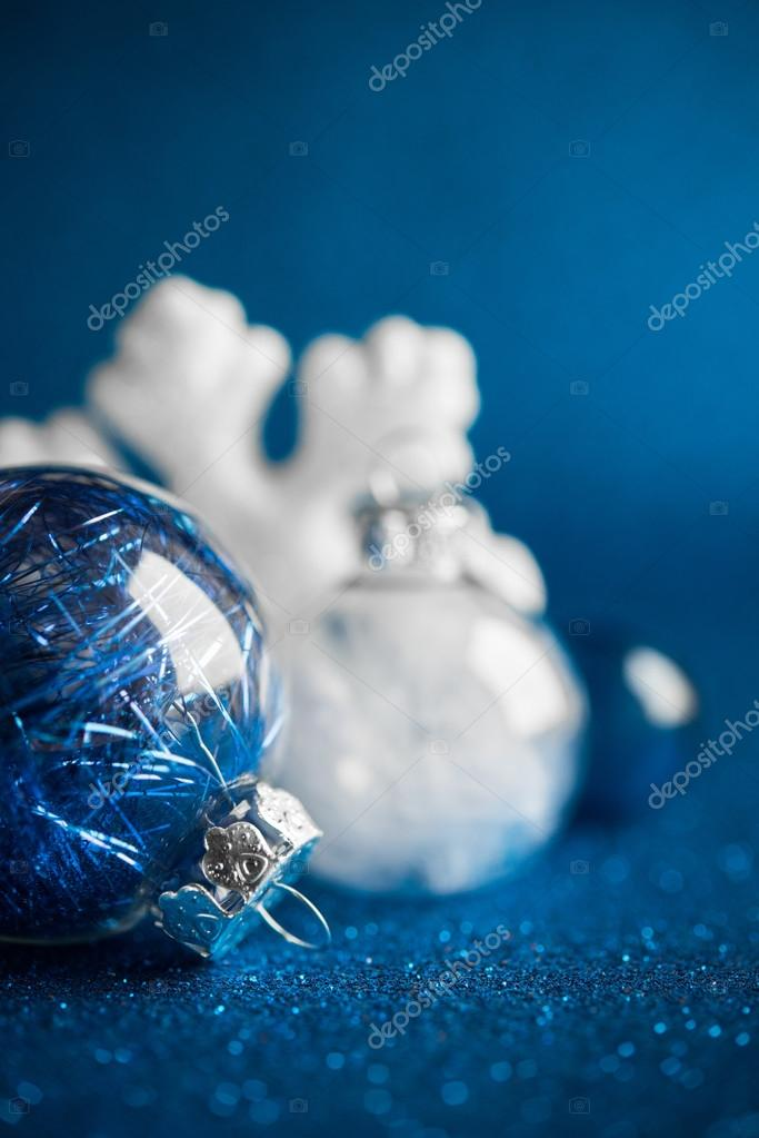 white and silver xmas ornaments on dark blue glitter background with space for text merry christmas card winter holiday theme elenadesigner