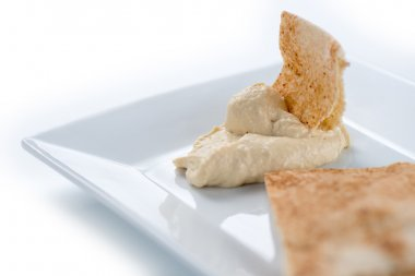Closeup of hummus with pita isolated against white