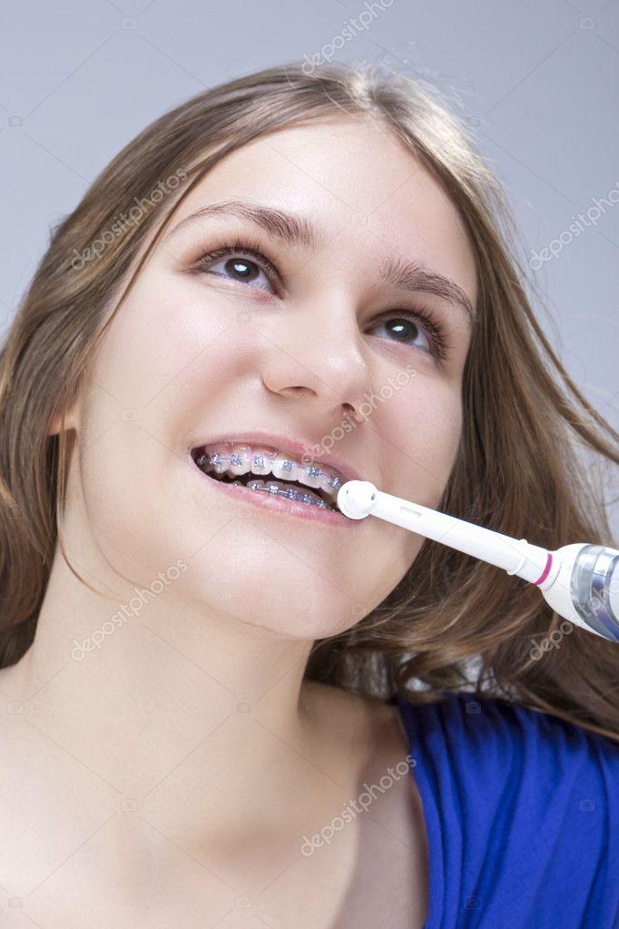 Closeup retrato de adolescente caucásico cepillado dientes soportes con  imagen de Toothbrush.Vertical eléctrico — Foto de dimamorgan12 5f6624171703