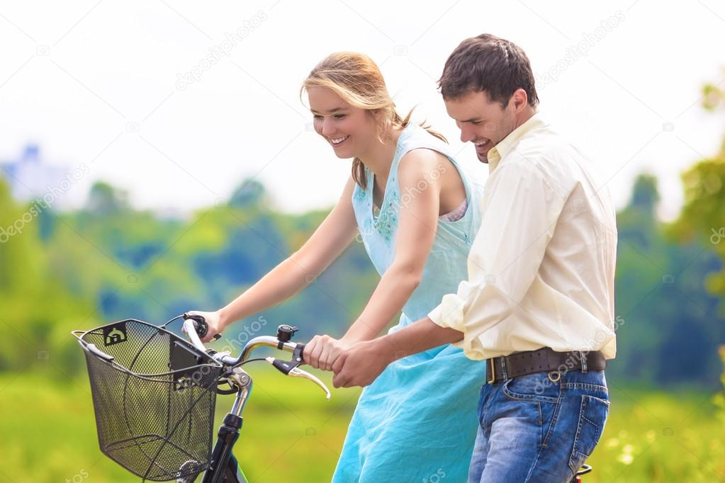 Happy Loving Caucasian Couple Having Fun Together Riding Bike Ou