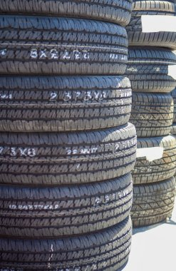 Stack of Brand New Automobile Black Tyres with Numbers Placed Ou