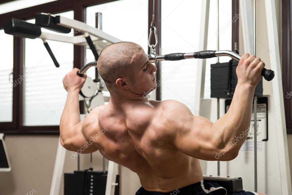 Gemeinsame Junger Mann Rücken Übungen auf einer Maschine — Stockfoto © ibrak @BG_94