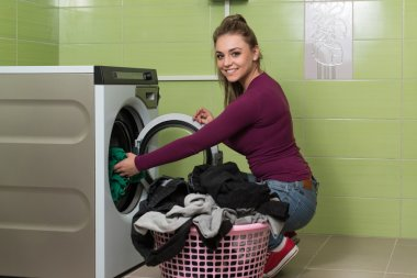 Young Woman Putting A Cloth Into Washing Machine