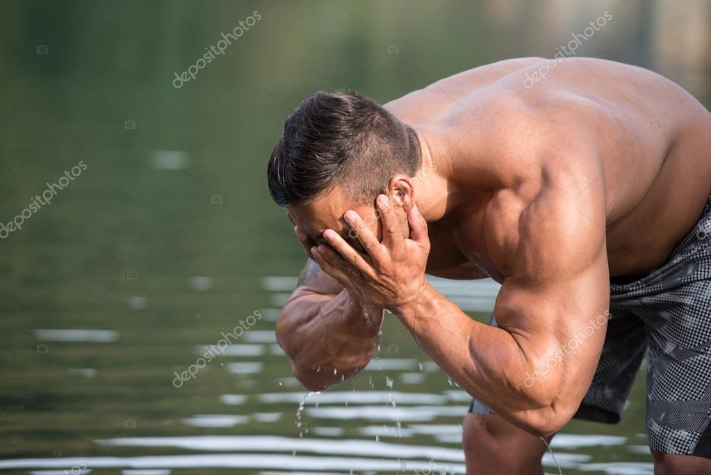 Attractive Man Washing His Face In River