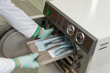 Dentist Places Medical Autoclave For Sterilising Surgical