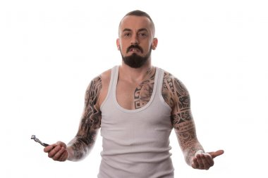 Tattooed Man Styling Beard Holding Disposable Razor