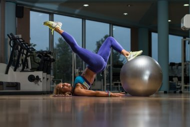 Mature Woman Doing Sit-Ups With Exercise Ball