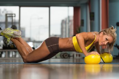 Woman Doing Push Up Exercise On Yellow Balls