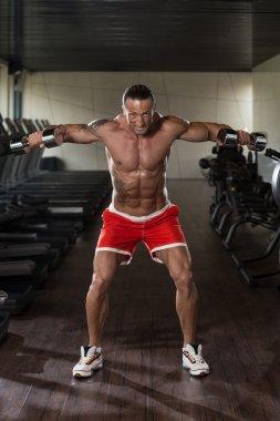 Bodybuilder Exercising Shoulders With Dumbbells