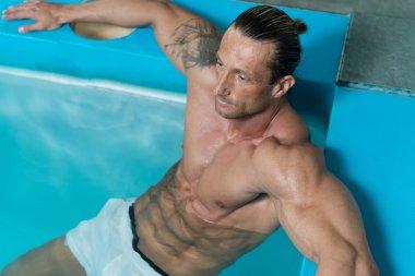 Mature Man Swimming In Pool At Resort