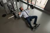 Fotografie Businessman Exercise Bench Press With Barbell