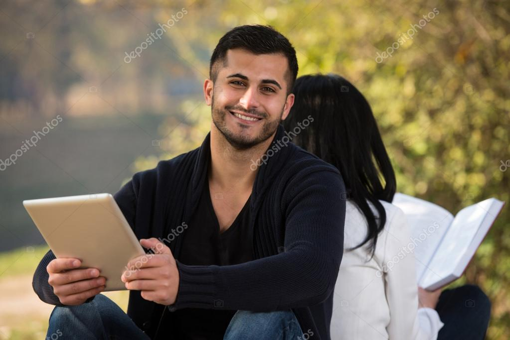 Couple Enjoying Digtial Tablet And Book