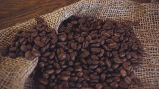 pražená kávová zrna na pytlovině na dřevěném stole