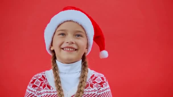 Mädchen mit Weihnachtsmütze und Weihnachtspullover spielt mit Zöpfen auf rotem Grund
