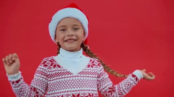 trauriges Mädchen mit Weihnachtsmütze und Weihnachtspullover auf rotem Grund