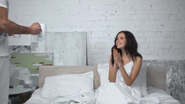 muž dává šálek šťastné ženě v posteli a sledování filmu