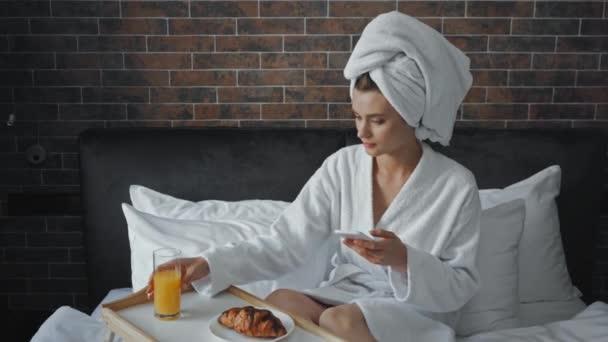 mladá žena v ručníku fotografování snídaně na podnosu v hotelu