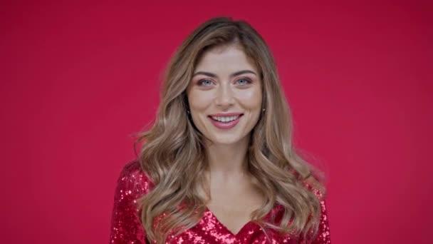 Usmívající se žena dívá na kameru izolované na červené