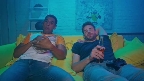 KYIV, UKRAINE - OCTOBER 20, 2020: Multiethnic friends with beer on couch at home