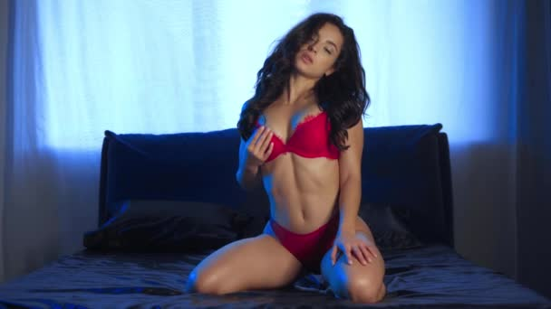 szexi nő piros fehérnemű megérinti magát, miközben pózol a fekete ágynemű
