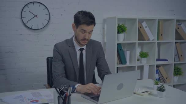 rozrušený podnikatel psaní na notebook a mluvení v kanceláři