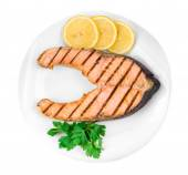 Salmon steak with lemon on plate