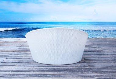 Wicker sunbed on a sea background