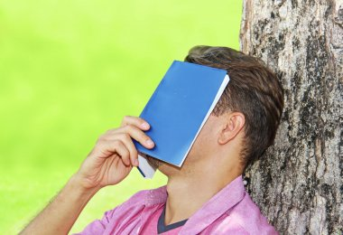 Young man covered his face with a book