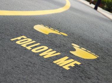 Follow me written on the road